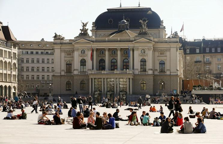 People enjoy the sunny weather as they sit on the Sechselaeutenplatz square in front of the opera house in Zurich March 20, 2014. Spring officially began on Wednesday in the northern hemisphere, and is known as both the spring or vernal equinox. REUTERS/Arnd Wiegmann