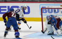 St. Louis Blues center Oskar Sundqvist, back, drives past Colorado Avalanche defenseman Conor Timmins, left, to score a goal against goaltender Philipp Grubauer in the third period of an NHL hockey game Wednesday, Jan. 13, 2021, in Denver. The Blues won 4-1. (AP Photo/David Zalubowski)