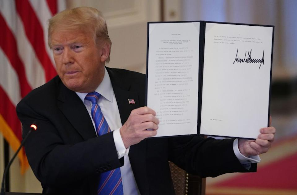 US President Donald Trump holds up an Executive Order he signed in June. Source: Getty