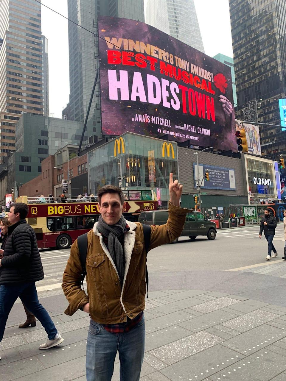 """Broadway actor John Krause poses in front of the """"Hadestown"""" billboard in Times Square just hours before his scheduled debut in the role of Orpheus. """"It's a very special moment in anyone's career so everyone was very excited. I had friends and family coming in and people had tickets for the whole week,"""" Krause said."""