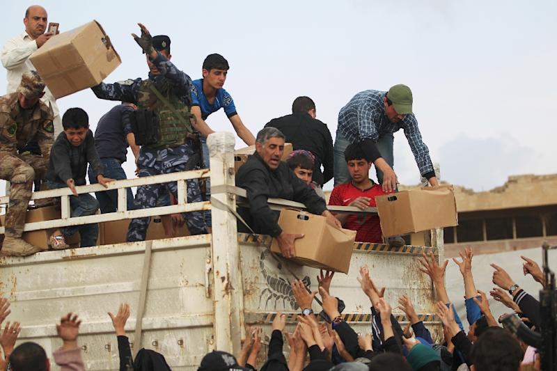 Iraqis displaced from Mosul surge forward to receive aid from a truck at Mamam al-Alil camp (AFP Photo/AHMAD AL-RUBAYE)