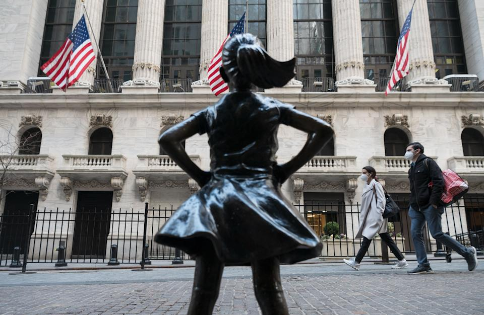 People walk past the New York Stock Exchange (NYSE) at Wall Street and the  'Fearless Girl' statue on March 23, 2021 in New York City. - Wall Street stocks were under pressure early ahead of congressional testimony from Federal Reserve Chief Jerome Powell as US Treasury bond yields continued to retreat. (Photo by Angela Weiss / AFP) (Photo by ANGELA WEISS/AFP via Getty Images)