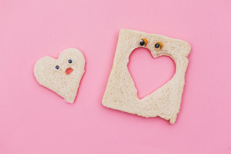 heart shape piece of bread couple in pink background (Photo: Carol Yepes via Getty Images)