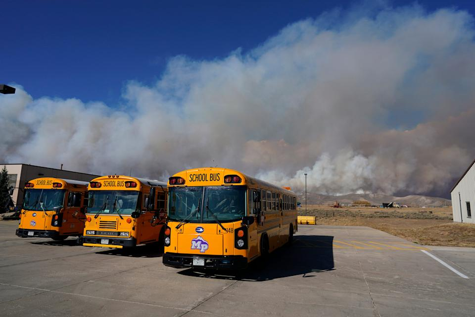 Smoke rises from mountain ridges as a wildfire burns while buses sit idle at the high school Thursday, Oct. 22, in Granby, Colorado.