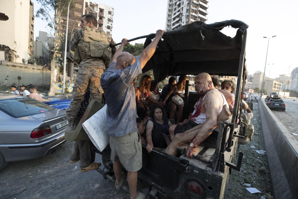 Injured people are evacuated after a massive explosion in Beirut, Lebanon, Tuesday, Aug. 4, 2020. (AP Photo/Hassan Ammar)