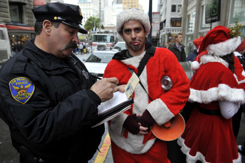 FILE - This Dec. 10, 2009 file photo shows a San Francisco Police officer giving a man dressed as Santa Claus an open container ticket during the Santacon pub crawl in downtown San Francisco.  SantaCon is coming to town _ in fact, to nearly 300 towns and cities around the world. Dozens, sometimes hundreds of red-suited revelers gather, bar hop, stop traffic and pose for photos.   (AP Photo/Russel A. Daniels, file)