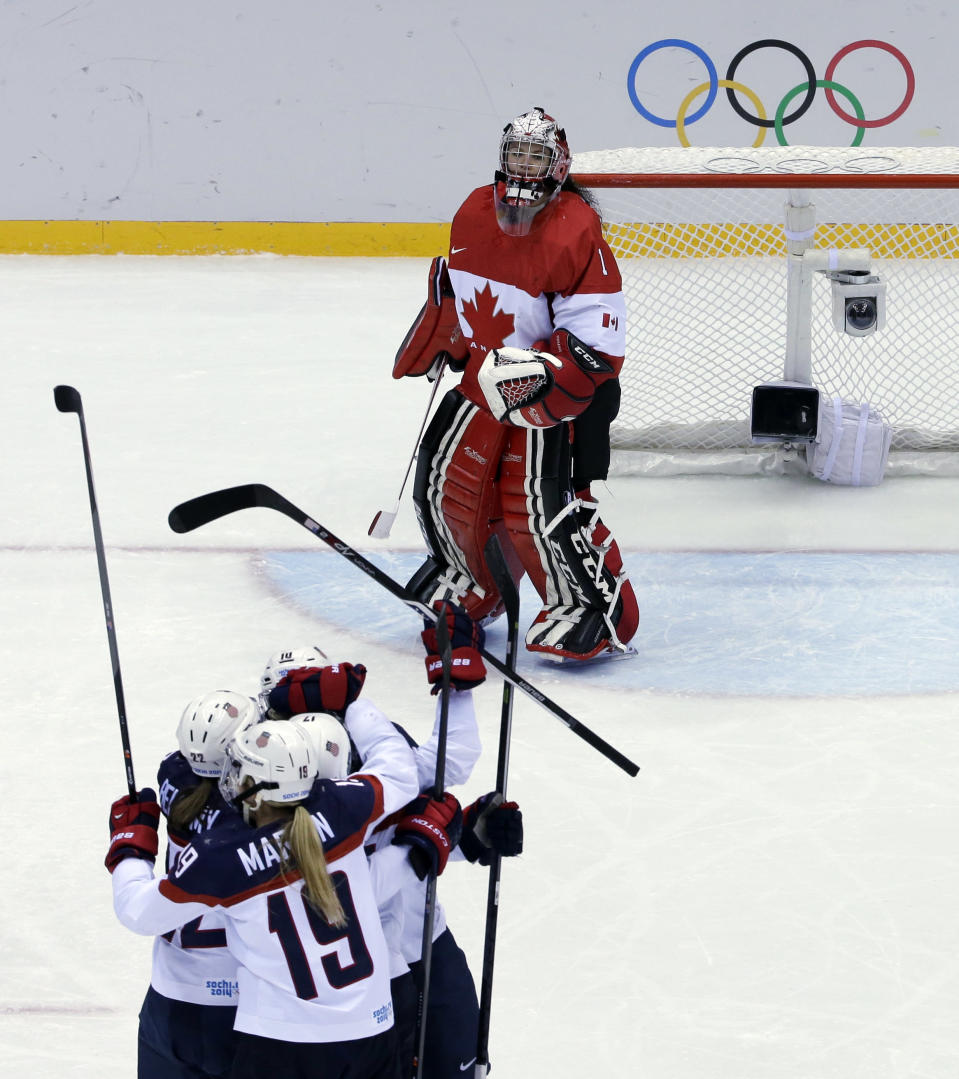 Goalkeeper Shannon Szabados of Canada (1) watches as Meghan Duggan of the United States is congratulated by teammates after scoring a goal during the women's gold medal ice hockey game at the 2014 Winter Olympics, Thursday, Feb. 20, 2014, in Sochi, Russia. (AP Photo/David J. Phillip )