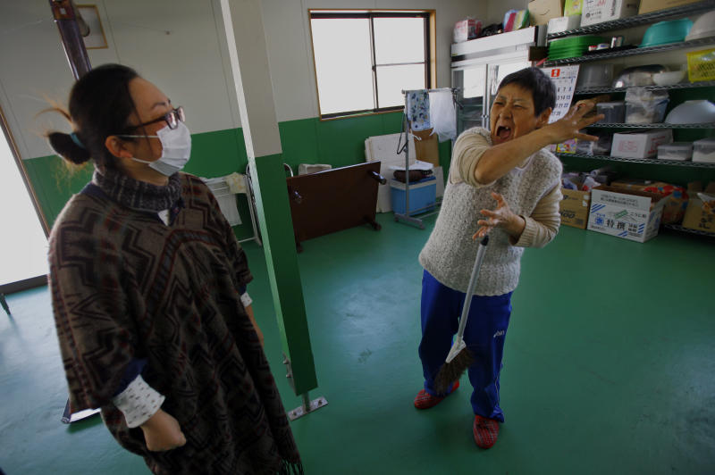 In this Monday, March 3, 2014 photo, Takako Sato, 62, right, a hearing impaired survivor of the March 11, 2011 tsunami, talks in sign language with Atsuko Takeshita, manager of Huck's House, a vocational center for the disabled, in Tanohata, Iwate Prefecture, northeastern Japan. The wait is just too much for Sato, who after nearly three years is fed up with the temporary housing. Hearing impaired, she waves her hands repeatedly to convey how her house was swept away, and holds them joined as if in prayer to express her frustrations. (AP Photo/Junji Kurokawa)