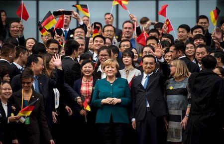 German Chancellor Merkel and Chinese Premier Li pose with students after their visit to the German University in Hefei