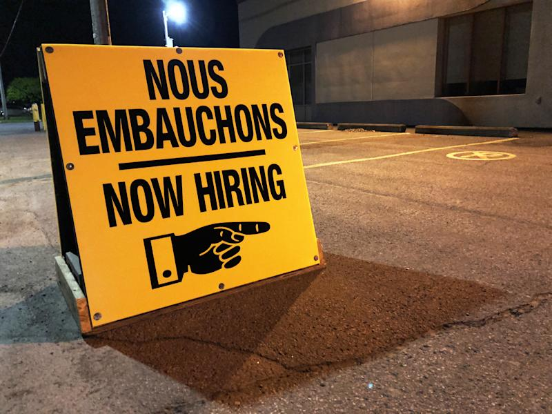 French and English Bilingual now hiring sign in front of a company in the morning