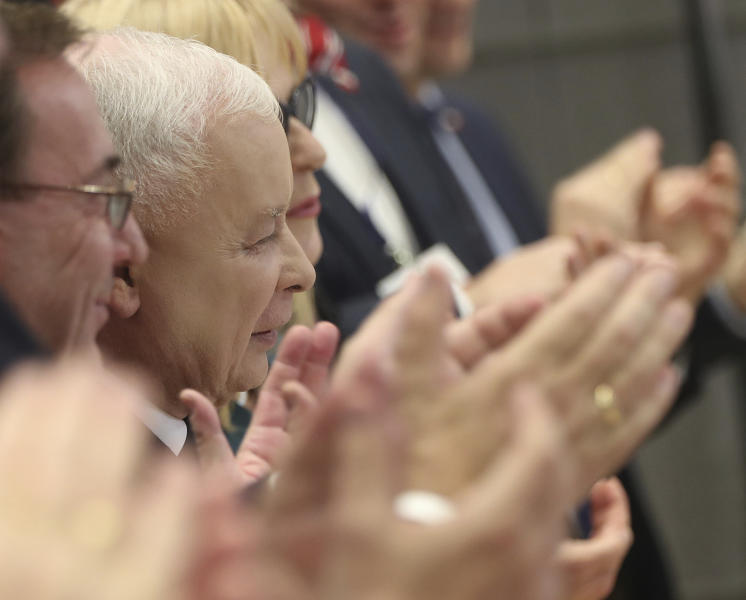 In this photo taken Tuesday Oct. 8, 2019 Poland's ruling right-wing party leader Jaroslaw Kaczynski,center, is applauded by party members after he spoke at a convention in Warsaw, Poland, ahead of Sunday parliamentary election in which his Law and Justice party is hoping to win a second term in power. (AP Photo/Czarek Sokolowski)