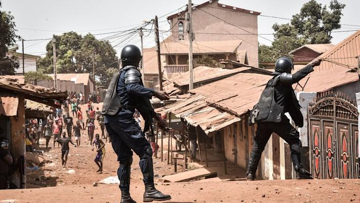 A policemen taking on protesters in a neighbourhood of Conakry, Guinea - 27 February 2020