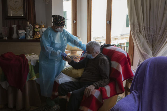 Nurse Pilar Rodríguez comforts Antonio Comas Serra, 80, after receiving the vaccine against COVID-19 at his home in the town of Sa Pobla on the Spanish Balearic Island of Mallorca, Spain, Friday, April 30, 2021. While thousands flock daily at health clinics and ad-hoc vaccination points across Spain, health workers also fan out across the country to take shots to some of those who are the most vulnerable to the coronavirus. (AP Photo/Francisco Ubilla)