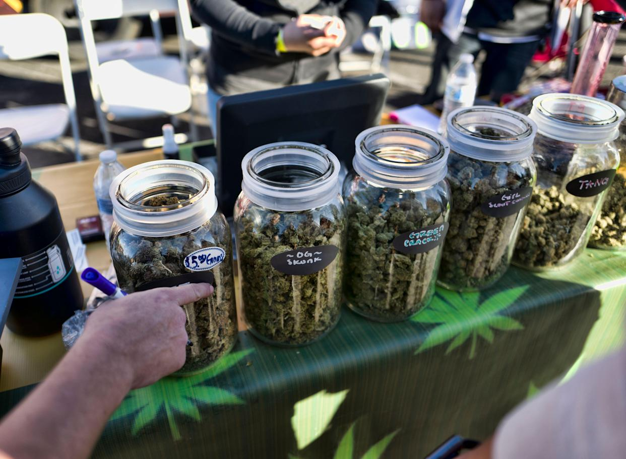 In this Saturday, Dec. 29, 2018 photo a vendor points to a selection of cannabis strains for sale during Kushstock 6.5 festival in Adelanto Calif. (AP Photo/Richard Vogel)
