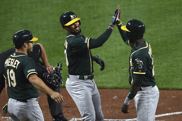 Oakland Athletics' Marcus Semien, center is congratulated by Jurickson Profar, right, and Josh Phegley after hitting a three run home run in the third inning of a baseball game, Tuesday, April 9, 2019, in Baltimore. (AP Photo/Gail Burton)