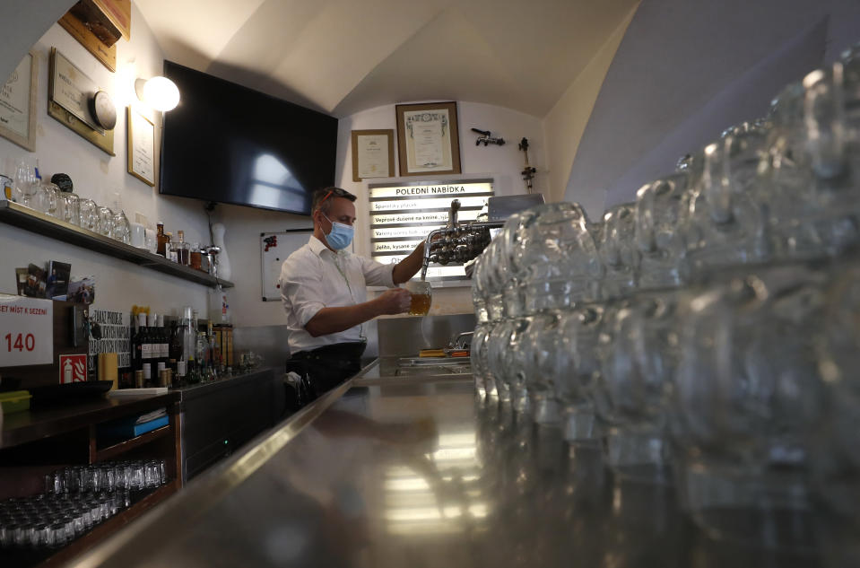 A bartender drafts a beer at a pub in Prague, Czech Republic, Thursday, Dec. 3, 2020. A sign of normalcy has returned to the Czech Republic ahead of the Christmas period after the government eased some of its most restrictive measures imposed to contain the recent massive surge of coronavirus infections. On Thursday all stores, shopping malls, restaurants, bars and hotels were allowed to reopen. (AP Photo/Petr David Josek)
