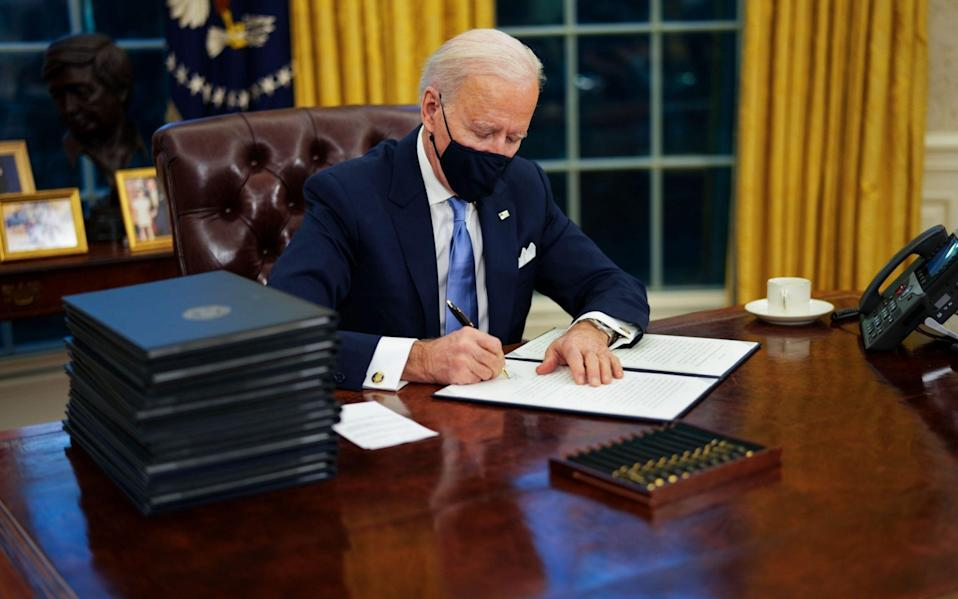 US President Joe Biden signs executive orders during his first minutes in the Oval Office, Washington, Usa - 19 Jan 2021 - EPA