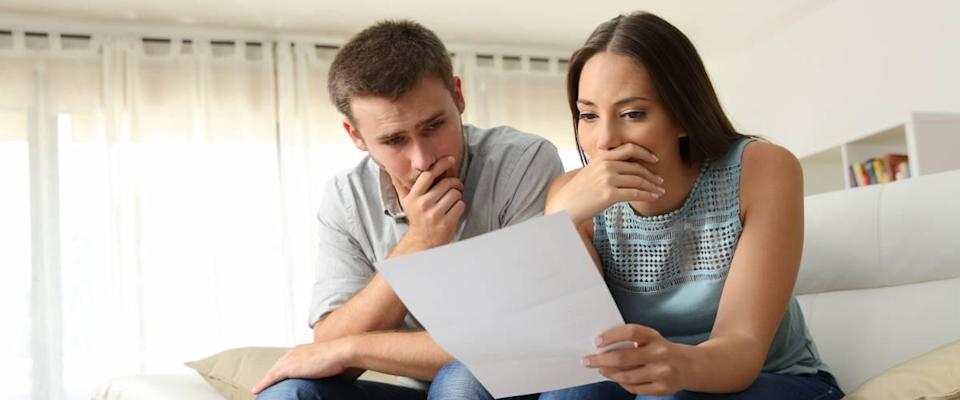 Worried couple reviewing loan agreement