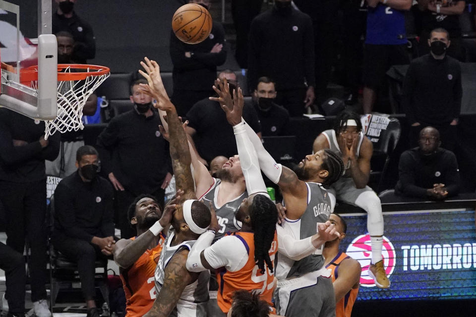 Members of the Los Angeles Clippers and Phoenix Suns battle for a rebound as the Clippers' guard Terance Mann, right, watches during the closing seconds in Game 4 of the NBA basketball Western Conference Finals Saturday, June 26, 2021, in Los Angeles. (AP Photo/Mark J. Terrill)
