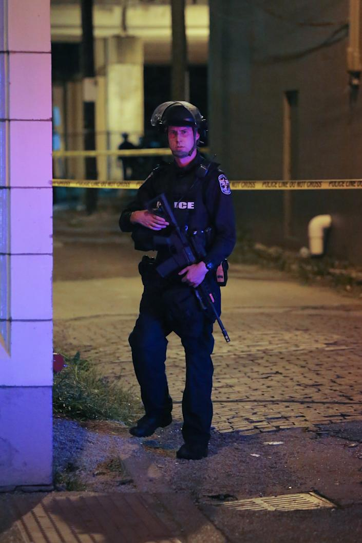 """A Louisville police officer stands guard with an AR-15 rifle at the scene near where two police officers were shot. <p class=""""copyright"""">Daniel Shular</p>"""