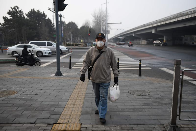 A man wears a face mask as he walks on a sidewalk in Beijing on February 13, 2020. - The number of deaths and new cases from China's COVID-19 coronavirus outbreak spiked dramatically on February 13 after authorities changed the way they count infections in a move that will likely fuel speculation that the severity of the outbreak has been under-reported. (Photo by GREG BAKER / AFP) (Photo by GREG BAKER/AFP via Getty Images)