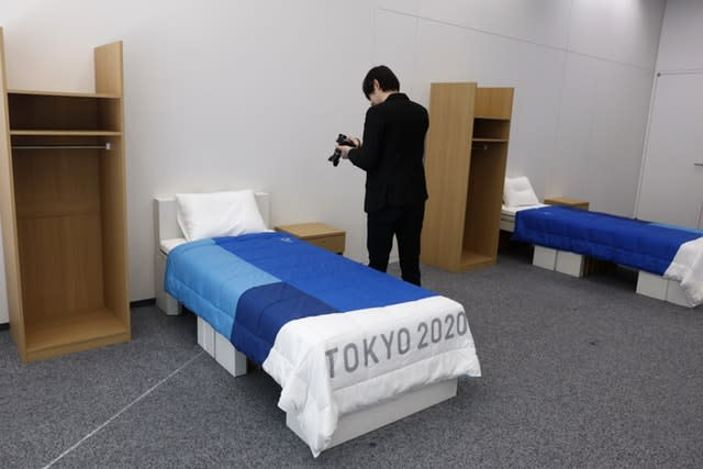 A journalist films a cardboard bed in a display room showing furniture for the Tokyo 2020 Olympic and Paralympic Villages