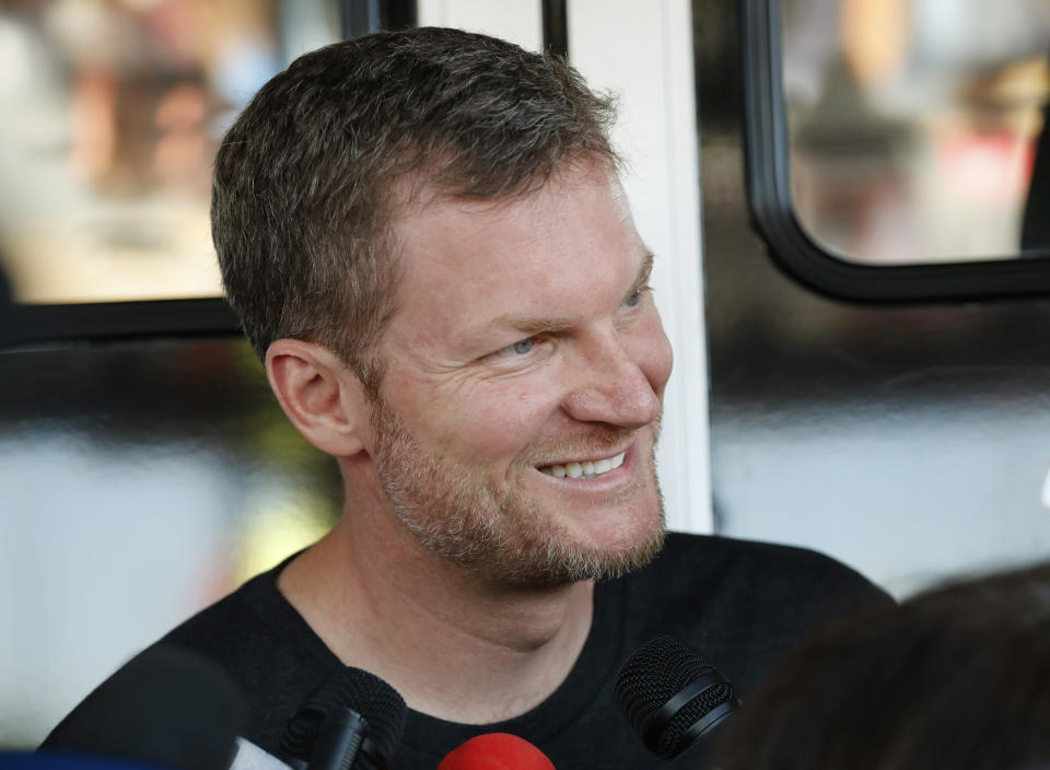 """FILE - Dale Earnhardt Jr. talks with the media in the garage area before practice for a NASCAR auto race in Darlington, S.C., in this Friday, Aug. 30, 2019, file photo. He's a 46-year-old married father of two daughters, a NASCAR Hall of Fame inductee and the 15-time fan-voted most popular driver. No matter all his personal bliss, Earnhardt still has social anxieties and was a wreck when NBC Sports launched its NASCAR coverage at Nashville with a heavily-promoted pre-race show that featured him alongside country star Brad Paisley. """"I was terrified,"""" Earnhardt told The Associated Press of the assignment. (AP Photo/Terry Renna, File)"""