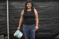 Elisa Xolalpa, who survived an acid attack while tied to a post by her ex-partner 20 years ago when she was 18, poses for a portrait in her greenhouse in Mexico City, Saturday, June 12, 2021. Survivors like Xolalpa want the attacks classified as attempted femicide, aid with the innumerable surgeries that follow and psychological support. (AP Photo/Ginnette Riquelme)