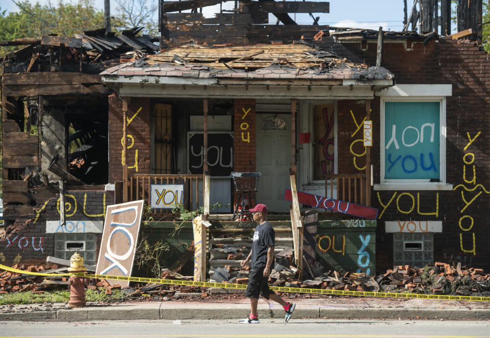 """The """"You"""" house at the Heidelberg Project in Detroit stands badly damaged after a fire early Monday, September 23, 2019. Arson investigators have a person of interest in custody and public safety officials are bringing out heavy equipment to knock down the house, part of the Heidelberg Project art installation. (David Guralnick/Detroit News via AP)"""