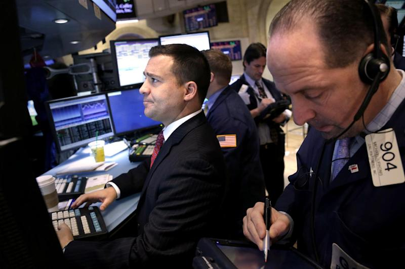 """Traders work on the floor at the New York Stock Exchange in New York, Monday, Dec. 31, 2012. The stock market struggled for direction Monday morning after five days of losses, with the """"fiscal cliff"""" just hours away and lawmakers yet to reach a solution. (AP Photo/Seth Wenig)"""