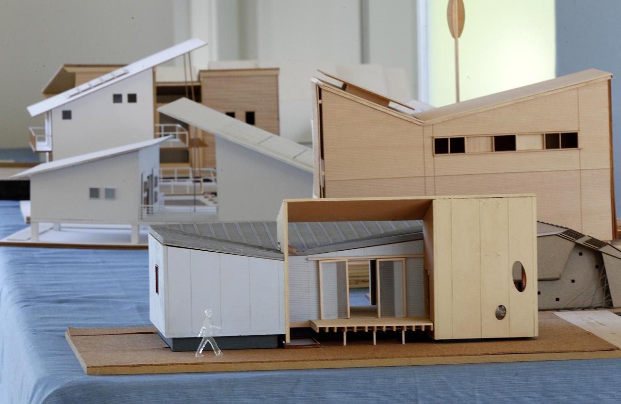ADVANCE FOR WEEKEND EDITIONS APRIL 21-22 - In a Thursday, April 5, 2012 photo, models that were submitted as part of a design competition to rebuild houses in New Orleans are seen with the winning entry, the Roese Sunshower SSIP house, in the foreground, in New Orleans. The house is meant to go up quickly after disasters and then serve as permanent housing that can withstand future calamities. It's designed to be environmentally friendly, survive outside damaged utility grids and can be shipped in pieces in a single container and assembled like an erector set. (AP Photo/Gerald Herbert)