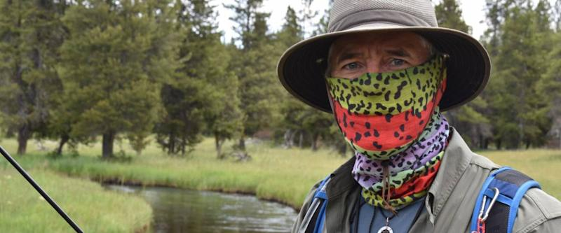 Attractive older Caucasian man with blue eyes, with face covered by bandana. Standing beside a river with fishing rod, trees and grass in background. He looks like a retiree.