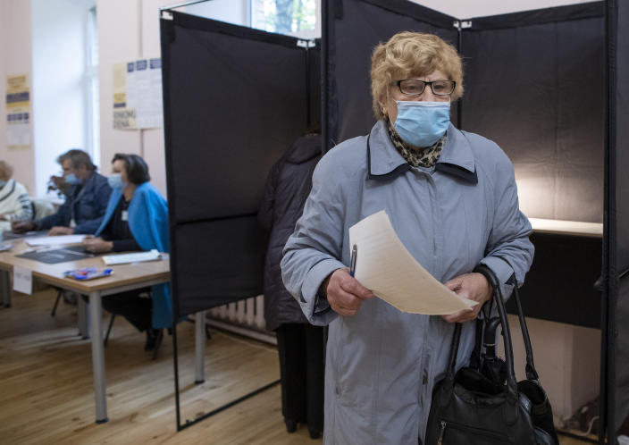 A Lithuanian woman, wearing a face mask to protect against coronavirus prepares to cast he ballot at a polling station during parliamentary elections in Vilnius, Lithuania, Sunday, Oct.11, 2020. Polls opened Sunday for the first round of national election in Lithuania, where voters will renew the 141-seat parliament and the ruling four-party coalition is widely expected to face a stiff challenge from the opposition to remain in office. (AP Photo/Mindaugas Kulbis)