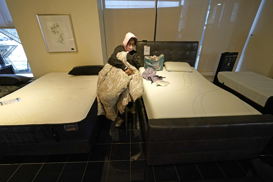 Dialina Gonzalez gathers her belongings after spending the night on a mattress inside a Gallery Furniture store which opened as a shelter Wednesday, Feb. 17, 2021, in Houston. Millions in Texas still had no power after a historic snowfall and single-digit temperatures created a surge of demand for electricity to warm up homes unaccustomed to such extreme lows, buckling the state's power grid and causing widespread blackouts. (AP Photo/David J. Phillip)