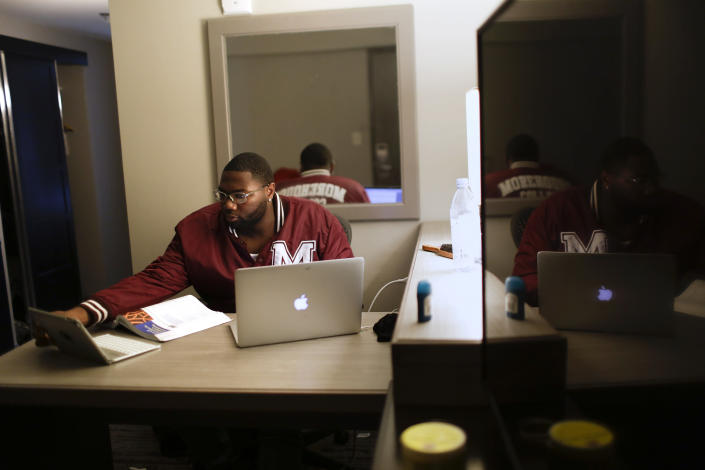 """In this Tuesday, May 5, 2020, photo, Morehouse College senior Lanarion """"LTL"""" Norwood Jr., of Atlanta, works on his computer in a hotel room in Atlanta. Students were sent home from the college amid the new coronavirus outbreak. Norwood learned the campus was shutting down and he was worried about going home to finish his senior year in a neighborhood he describes as """"gang-ridden, drug-ridden, all over violence-ridden."""" Morehouse stepped up with a plan, working to house about 20 students. (AP Photo/Brynn Anderson)"""