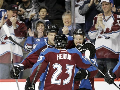 Colorado Avalanche defenseman Ryan O'Byrne, left, and right wing Milan Hejduk (23), of the Czech Republic, congratulate Avalanche left wing TJ Galiardi after he scored against the Minnesota Wild in the first period of their NHL hockey game on Tuesday, Jan. 24, 2012, in Denver. (AP Photo/Joe Mahoney)