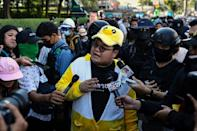Pro-democracy activist Parit 'Penguin' Chiwarak, wearing a duck cap, is one of the 12 protest leaders called in for questioning