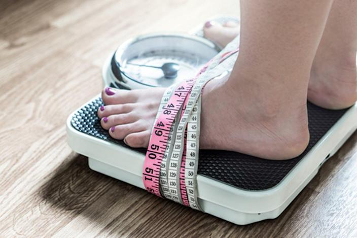 """<span class=""""caption"""">Weighing oneself often becomes a trap for those with eating disorders.</span> <span class=""""attribution""""><a class=""""link rapid-noclick-resp"""" href=""""https://www.shutterstock.com/image-photo/feet-tied-measuring-tape-weight-scale-668247181?src=DNymoX69upd5ZTL3kiSrpw-1-1"""" rel=""""nofollow noopener"""" target=""""_blank"""" data-ylk=""""slk:Tero Vesalainen/Shutterstock.com"""">Tero Vesalainen/Shutterstock.com</a></span>"""