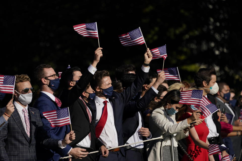 Staffers wave as President Donald Trump walks to board Marine One on the South Lawn of the White House, Wednesday, Oct. 14, 2020, in Washington. (AP Photo/Evan Vucci)