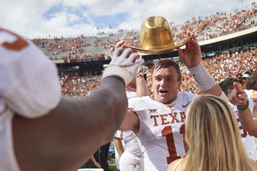 Texas quarterback Sam Ehlinger (11) holds the Golden Hat as he celebrates with teammates after defeating Oklahoma 48-45 at the Cotton Bowl on Saturday in Dallas. (AP Photo/Cooper Neill)