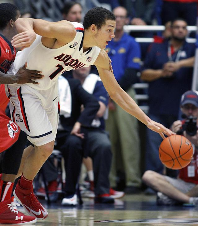 Arizona's Aaron Gordon (11) struggles with Utah's Delon Wright, left, as he drives toward the basket in the second half of an NCAA college basketball game on Sunday, Jan. 26, 2014, in Tucson, Ariz. (AP Photo/John Miller)