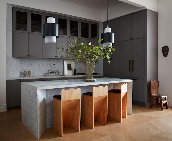 A 1950s French concrete vase sits on the marble island in the kitchen that Valle designed, along with the wood counter stools. The suspended lamps are Dutch from the 1960s; a carved wood child's chair from the 1920s stands in the corner, and on the counter are a pair of alabaster vases and a framed work by Ed Ruscha.