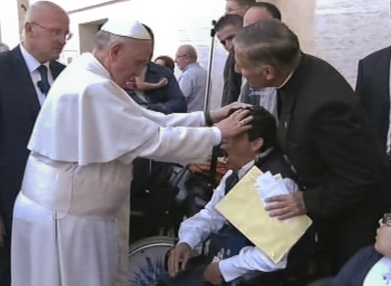 "In this image made from video provided by APTN, Pope Francis lays his hands on the head of a young man on Sunday, May 19, 2013, after celebrating Mass in St. Peter's Square. The young man heaved deeply a half-dozen times, convulsed and shook, and then slumped in his wheelchair as Francis prayed over him. The television station of the Italian bishops' conference said it had surveyed exorcists, who agreed Francis either performed an exorcism or a prayer to free the man from the devil. The Vatican was more cautious Tuesday, saying Francis ""didn't intend to perform any exorcism. But as he often does for the sick or suffering, he simply intended to pray for someone."" (AP Photo/APTN)"