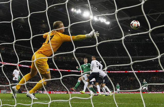 Germany's Per Mertesacker, center, scores pass England's goalkeeper Joe Hart, left, during the international friendly soccer match between England and Germany, at Wembley Stadium in London, Tuesday, Nov. 19, 2013. (AP Photo/Alastair Grant)