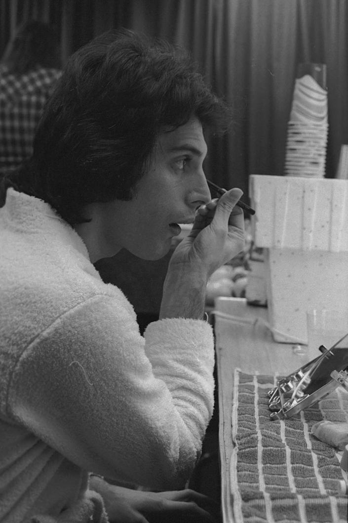 <p>Freddie Mercury of Queen applies make-up backstage before a concert in the US, January 1977.</p>