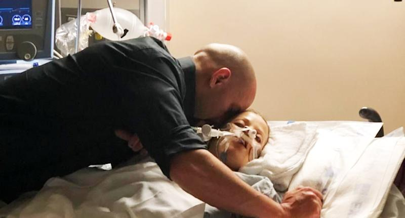 Zach Kincaid kisses his wife Krystil as she remains on life support after the crash.