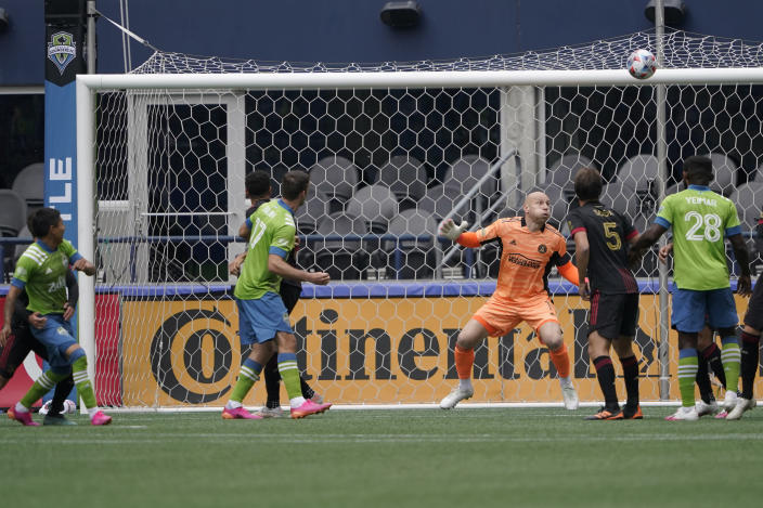 Atlanta United goalkeeper Brad Guzan, center, watches as a goal kicked by Seattle Sounders forward Raul Ruidiaz, left, heads for the corner of the net during the first half of an MLS soccer match, Sunday, May 23, 2021, in Seattle. (AP Photo/Ted S. Warren)