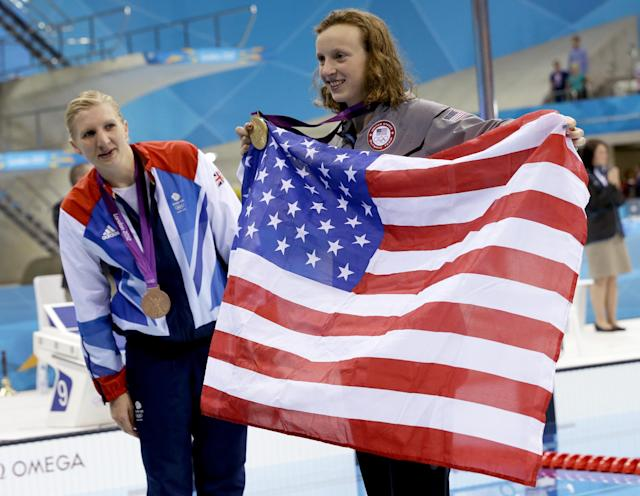 United States' Katie Ledecky, gold medalist in the women's 800-meter freestyle swimming final, right, holds an American flag and Britain's silver medalist Rebecca Adlington looks on at the Aquatics Centre in the Olympic Park during the 2012 Summer Olympics in London, Friday, Aug. 3, 2012. (AP Photo/Lee Jin-man)