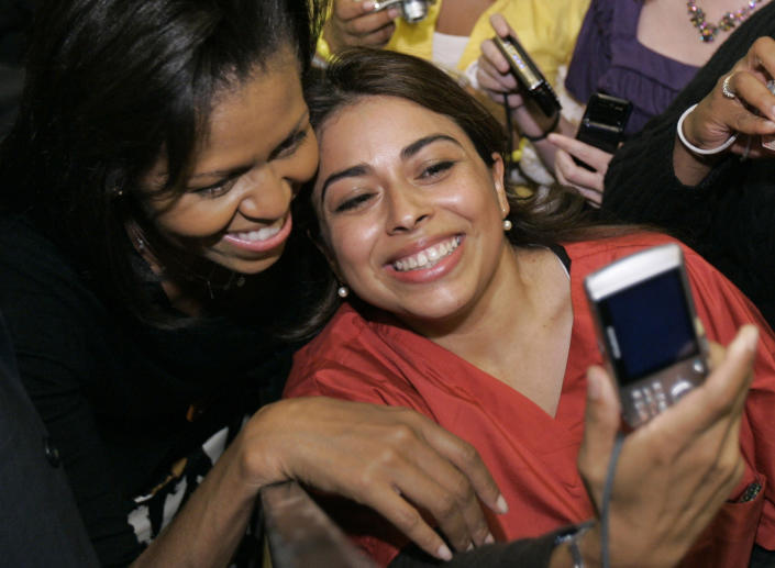 """File - In this Friday, Oct. 24, 2008, file photo Michelle Obama, left, wife of Democratic presidential candidate Sen. Barack Obama, D-Ill., takes a picture with a supporter after speaking at a rally at Buchtel High School in Akron, Ohio. Selfie"""" the smartphone self-portrait has been declared word of the year for 2013 by Britain's Oxford University Press. (AP Photo/Tony Dejak, File)"""