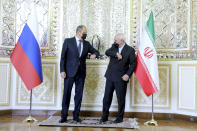 In this photo released by the Iranian Foreign Ministry, Iranian Foreign Minister Mohammad Javad Zarif, right, and Russian Foreign Minister Sergey Lavrov greet each other by touching elbows and wear face masks to curb the spread of COVID-19 prior to their talks in Tehran, Iran, Tuesday, April 13, 2021. Iran's foreign minister warned Tuesday that an attack on its main nuclear enrichment site at Natanz affects ongoing negotiations in Vienna over its tattered atomic deal with world powers. (Iranian Foreign Ministry via AP)